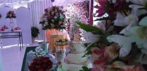 Salão Kid Festas - Flores ao fundo mesa com bolo